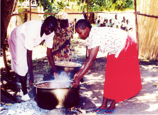 Academy staff cooking in large pots over open fires